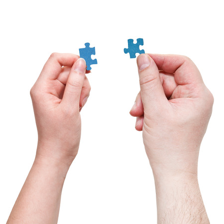male and female hands holding blue puzzle pieces isolated on white background