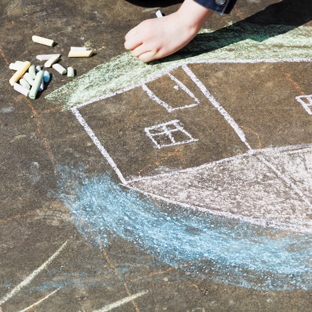 girl paints a house with colored chalk on asphalt outdoors photo