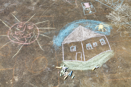 child drawing - house and sun painted on asphalt by colored chalk photo