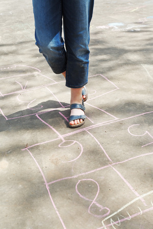 girl hopping in hopscotch outdoors in sunny day photo