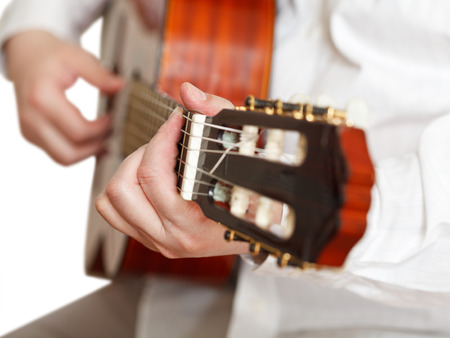 pegheads: man plays on classical acoustic guitar close up