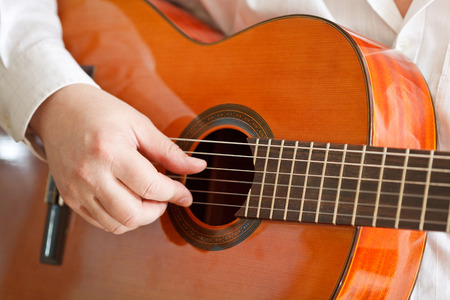 man playing classical acoustic guitar close up photo