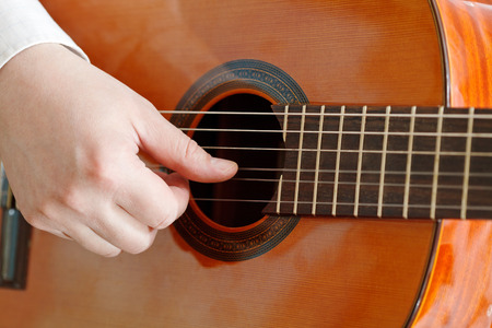 male hand plays on acoustic guitar close up isolated on white background photo