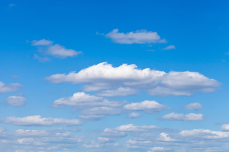 little fluffy white clouds in blue sky in May photo