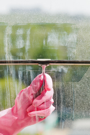 hand in pink glove cleans home window pane by squeegee in spring day photo
