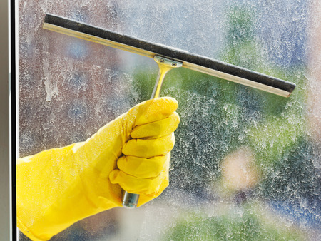 hand in yellow glove washes home window glass by squeegee in spring day photo