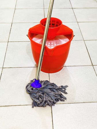 red bucket with foamy water and mop the tile floors photo