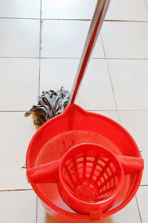 red bucket with washing water and mopping the tile floors photo