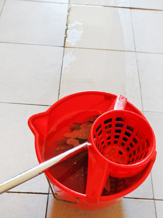 mop in red bucket with foamy water and washing the tile floor photo