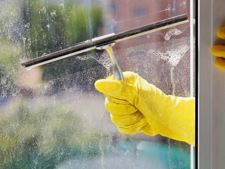 hand in yellow glove cleans home window glass by squeegee in spring day photo