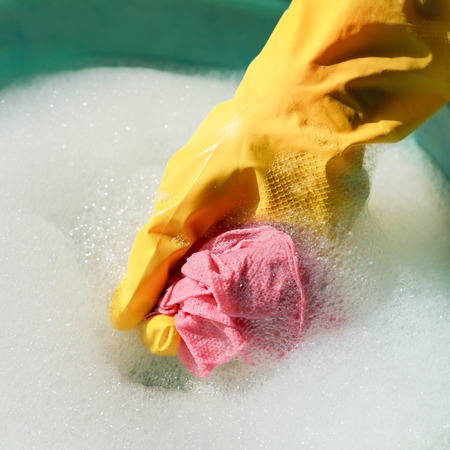 rinsing: hand in yellow rubber glove rinsing wet duster in soapy water