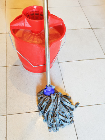 foamy: red bucket with foamy water and mopping the tile floors Stock Photo