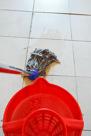 cleaning the tile floor by swab and red bucket with washing water photo