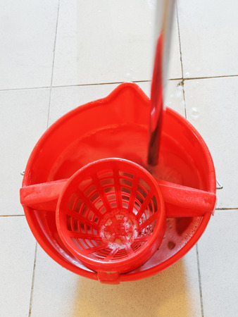 mop in red bucket with washing water on tile floor photo