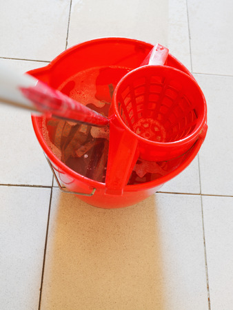 swab in red bucket with foamy water on tile floor photo