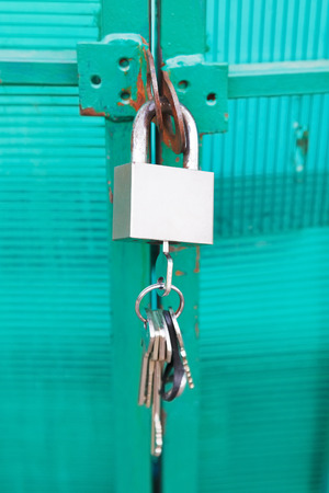 green door locked with padlock and bunch of keys photo