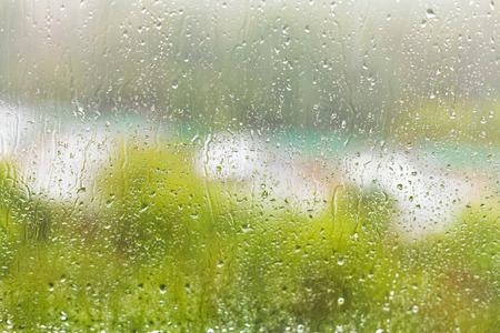 drizzling rain: rain outside window - raindrops on windowpane in summer day Stock Photo