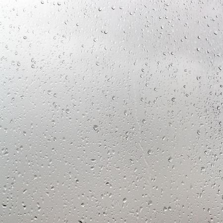 background from rain drops on window pane in cloudy day photo