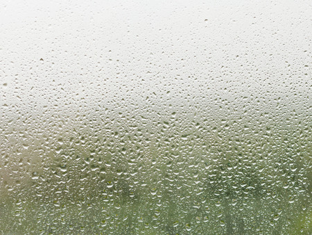 soppy: rain drops on home window pane with green forest and grey sky background Stock Photo