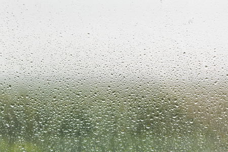 raindrops on home window glass with green forest and grey sky background