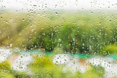 drizzling rain: raining outside window - rain drops on window glass in summer day