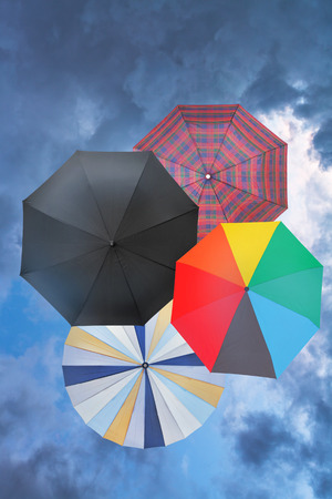 four open umbrellas with blue rainy clouds background photo