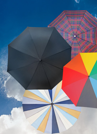 four different open umbrellas with cloudy dark blue sky background photo