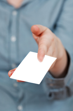 blank business card in between fingers close up photo