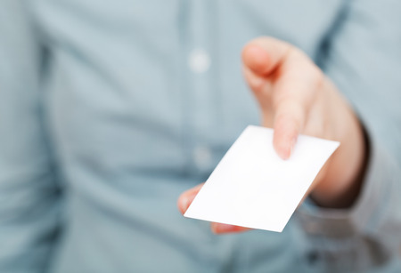 white business card in between female fingers close up photo