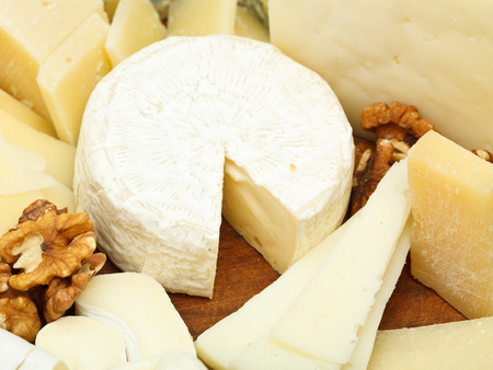 various cheeses on wooden plate close up photo