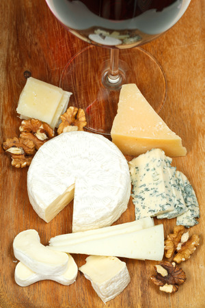 glass of red wine and various cheeses on wooden plate close up photo