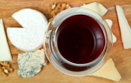 top view of glass of red wine and various cheeses on wooden plate close up photo