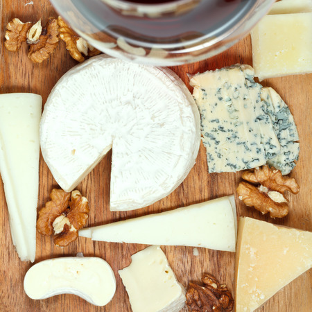 top view of red wine glass and assorted cheeses on wooden plate close up photo