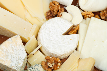 assortment of cheeses on wooden plate close up photo