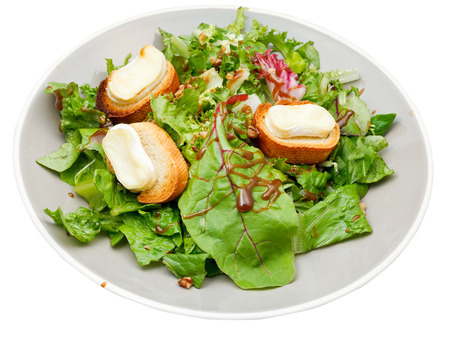 green salad with goat cheese on plate isolated on white background photo