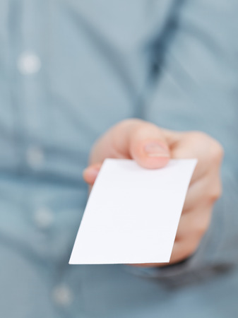 front view of blank business card in fingers close up photo