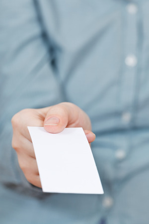 front view of blank business card in female hand close up photo