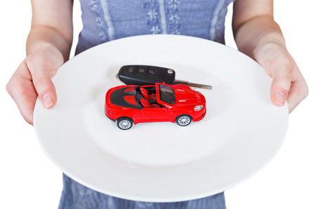 woman holds white plate with new red car isolated on white background photo