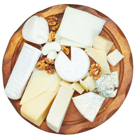 top view of wooden plate with various cheeses isolated on white background photo