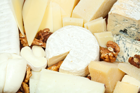 assortment of sliced cheeses and walnuts on plate close up photo