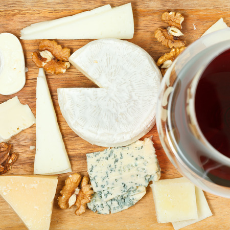 assorted cheeses on wooden plate close up photo