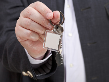 front view of businessman hand with blank door keychain close up photo