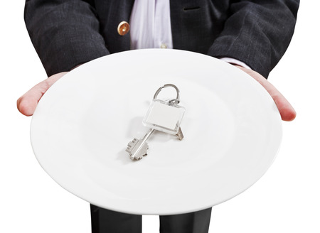 front view of businessman holds white plate with new door keys isolated on white background photo
