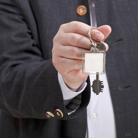 front view of male hand with blank door keychain close up photo