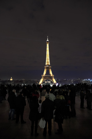 ascended: PARIS, FRANCE - DECEMBER 10, 2011: Tourist on champ de mars and night illumination of Eiffel Tower, Paris. Tower is most-visited paid monument in the world - 6.98 million people ascended it in 2011. Editorial