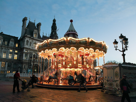 christmas in the city: PARIS, FRANCE - DECEMBER 13, 2011: Christmas illuminations of traditional carousel at Place de Hotel de Ville in Paris, France. First French example of carousel was in Paris in 1605.