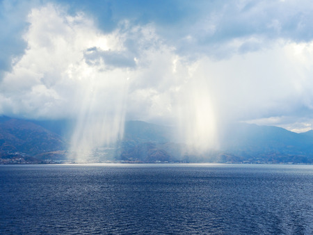 rays of sun breaking through clouds near coastline of Calabria, Italy coastline in Strait of Messina photo
