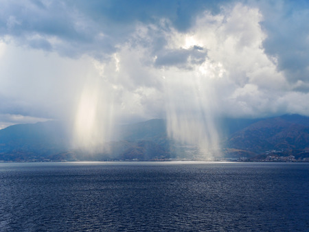 light of sun come through clouds near coastline of Calabria, Italy coastline inStrait of Messina photo