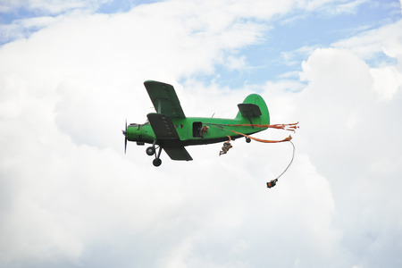 parachuting: parachuting jump from small green aircraft in white clouds