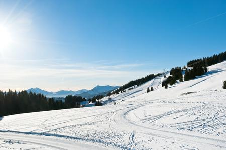 soleil: snow road and ski track near Avoriaz town in Alps, Portes du Soleil region, France